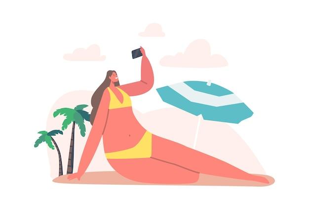 야자수와 우산이 있는 바다 해변에서 스마트폰으로 셀카를 찍는 젊은 여성. 여름 방학에 행복한 소녀