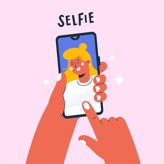 スマートフォンで自分撮り写真を撮る若い女性。