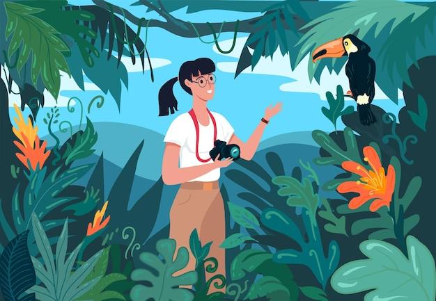 Молодая туристка фотографирует тукана дикой птицы в тропических джунглях