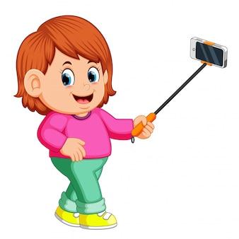 Молодая женщина, используя selfie stick