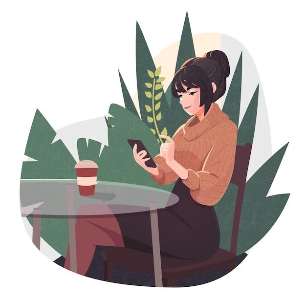 スマートフォンを使用して働く若い女性と屋外カフェでコーヒーを飲む