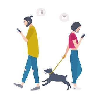 Молодая женщина выгуливает собаку на поводке и мужчина, проходя мимо друг друга, глядя на свои мобильные телефоны и проверяя социальные сети