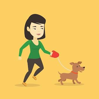 Молодая женщина гуляя с ее собакой