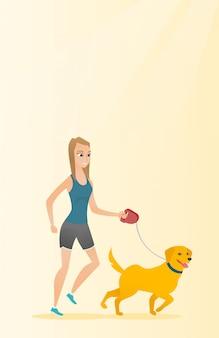 彼女の犬を連れて歩いて若い女性。