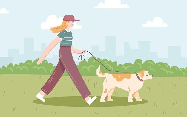 若い女性は、街を背景にひもにつないで犬と一緒に歩く