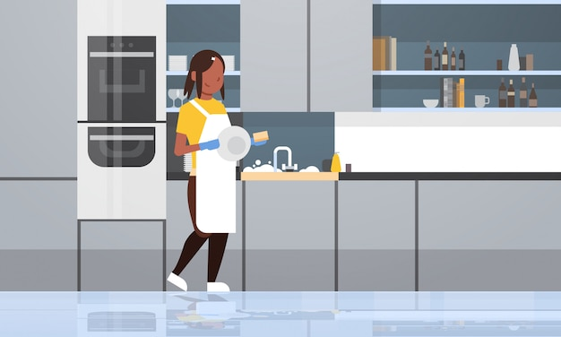 Young woman washing dishes   girl wiping plates dishwashing concept housewife doing housework modern kitchen interior  horizontal full length