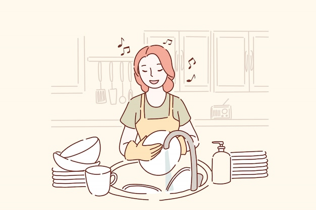 Young woman washing dishes and listening to music in the kitchen in a good mood.