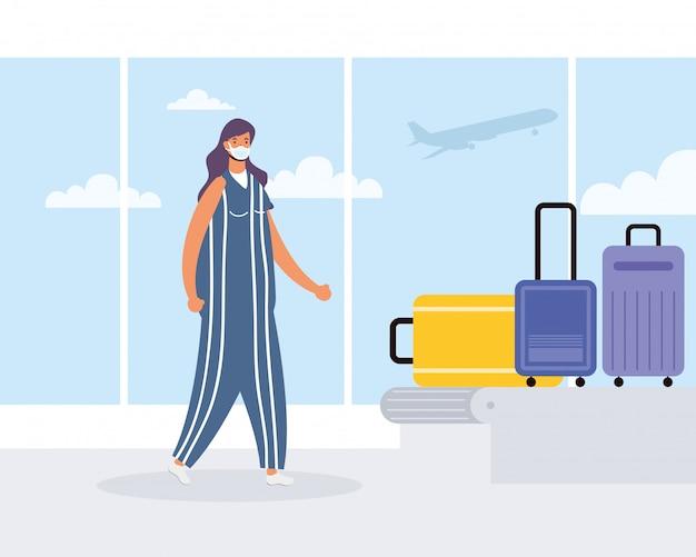 Молодая женщина в медицинской маске с чемоданами в транспортной группе