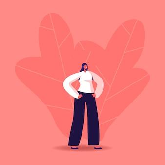 モダンなフォーマルな服を着た若い女性は、腰に腕を腰に当てて立っています。