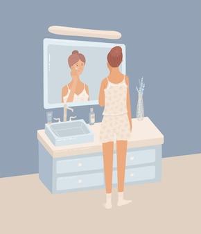 Молодая женщина в пижаме наносит ночной крем на кожу в ванной комнате