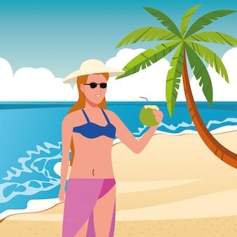 Молодая женщина в купальнике пьет кокосовый коктейль