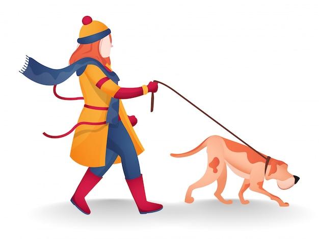 모직 옷을 입고 포즈를 걷는 개 가죽 끈을 잡고 젊은 여자.