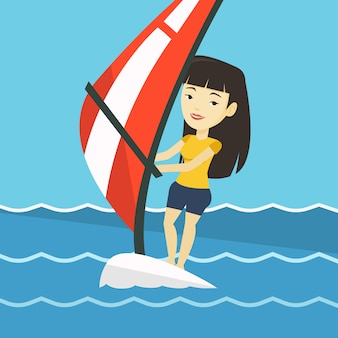 Young woman windsurfing in the sea.