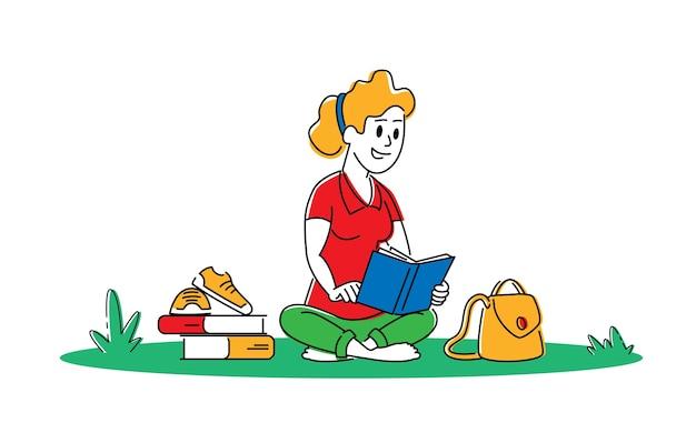 Молодая женщина с книгой сидит на траве готовится к экзамену или делает домашнее задание