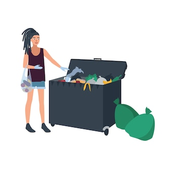 Young woman with dreadlocks picking leftover food from garbage container or trash bin.