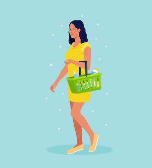 슈퍼마켓에서 음식과 음료로 가득 찬 쇼핑 바구니를 든 젊은 여성