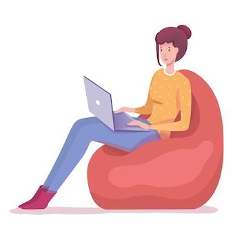 インターネットを介してリモートジョブに従事しているソフトアームチェアバッグフリーランサーに座ってラップトップに取り組んでいる若い女性