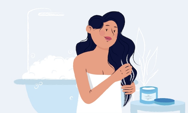 Young woman wrapped in a towel in her bathroom applying mask from the jar on her wet long hair after the shower.