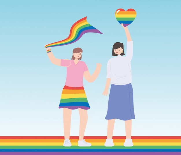 Young women holding rainbow heart and flag