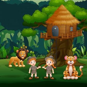 樹上の家の下で動物と遊ぶ飼育係の子供たち