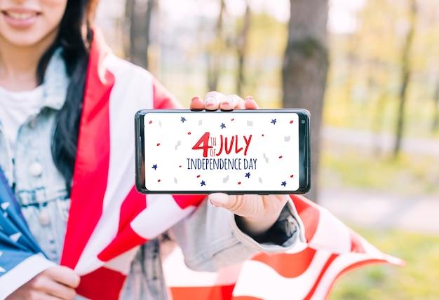 4. juli unabhängigkeitstag der vereinigten staaten von amerika. frau, die ein smartphone anhält