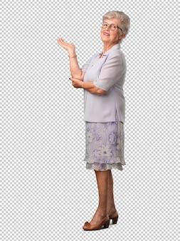 Ältere frau des vollen körpers, die etwas mit den händen hält, ein produkt zeigt, und fröhlich lächelt und einen eingebildeten gegenstand anbietet