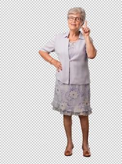 Ältere frau des vollen körpers, die nummer eins, symbol der zählung, konzept von mathematik, überzeugt und nett zeigt