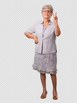 Ältere frau des vollen körpers, die nummer zwei, symbol der zählung, konzept von mathematik zeigt, überzeugt und nett