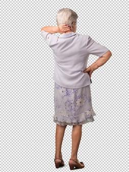 Ältere frau des vollen körpers, die zurück darstellt, aufwirft und wartet und zurück schaut