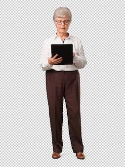 Ältere frau des vollen körpers lächelnd und überzeugt, eine tablette halten, sie verwendend, um das internet zu surfen und social media zu sehen, kommunikationskonzept