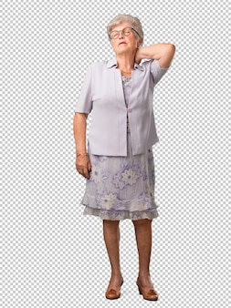 Ältere frau des vollen körpers mit den rückenschmerzen wegen des arbeitsstresses, müde und scharfsinnig