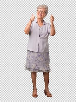 Ältere frau des vollen körpers nett und aufgeregt, lächelnd und ihren daumen oben anheben