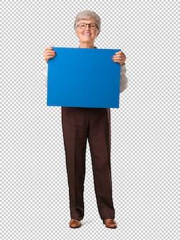 Ältere frau des vollen körpers nett und motiviert, ein leeres plakat zeigend