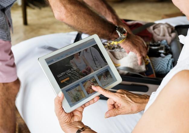 Ältere frau, die eine tablette auf dem bett verwendet