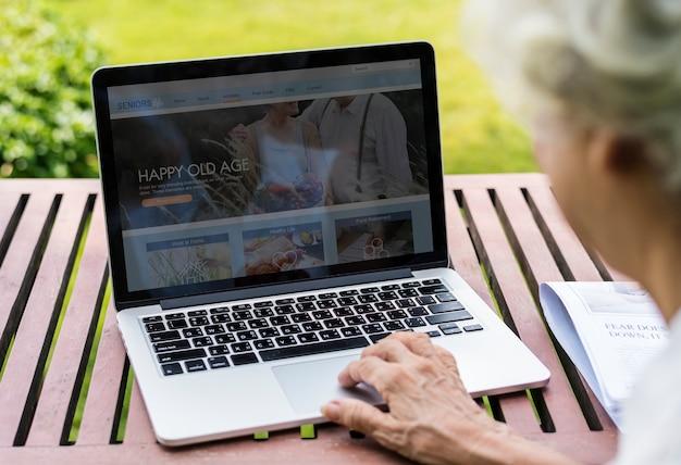 Ältere frau, die im urlaub einen laptop verwendet