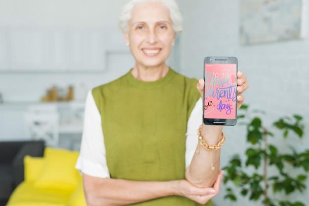 Ältere frau, die smartphonemodell hält