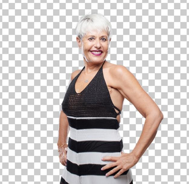 Ältere kühle frau, die stolz und sicher mit den armhänden auf hüften in der akimbo haltung lächelt