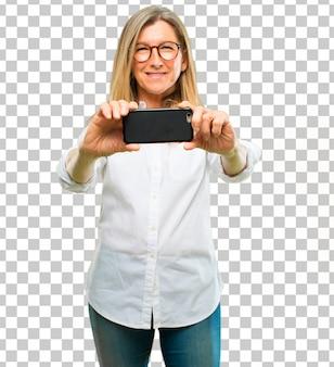 Ältere schöne frau mit einem intelligenten touch screen telefon