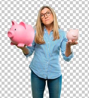 Ältere schöne frau mit einem sparschwein