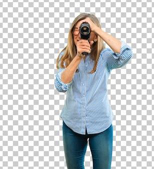Ältere schöne frau mit einer weinlesekino-kamera
