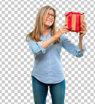 Ältere schöne frau mit geschenkboxkonzept