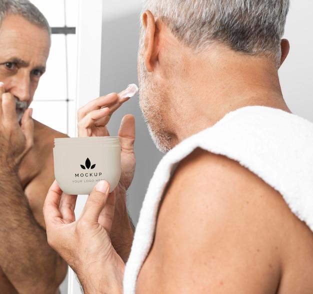 Älterer mann, der gesichtscreme anwendet