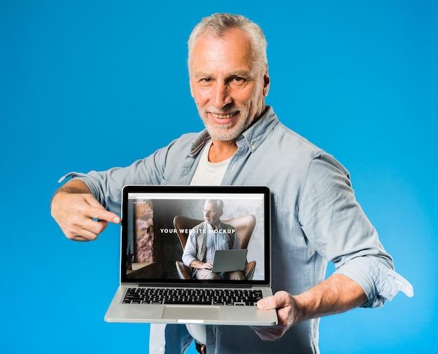 Älterer mann, der laptopmodell darstellt