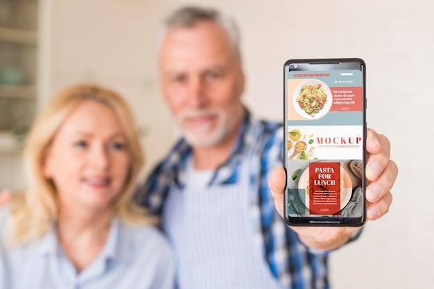 Älteres paar in der küche, die smartphone-modell hält