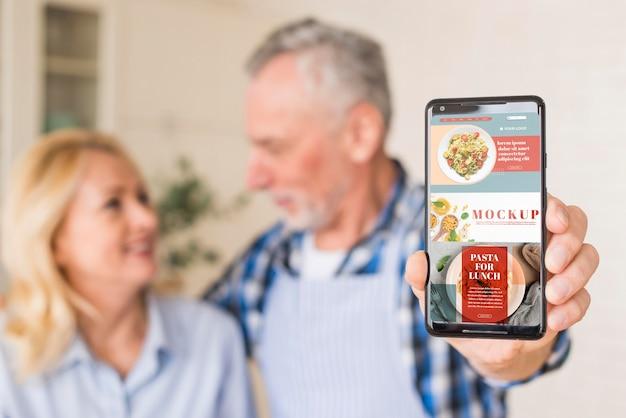 Älteres paar in der küche, die telefonmodell hält