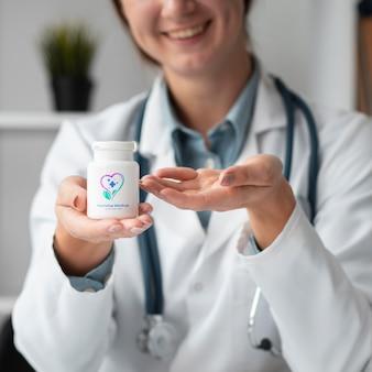 Ärztin, die eine modellmedizinflasche hält