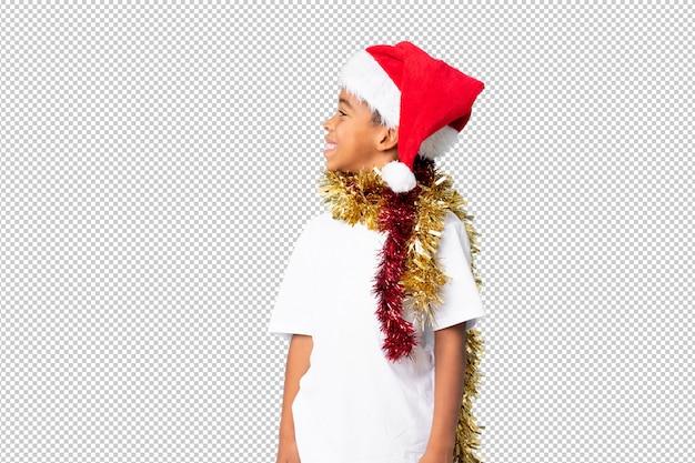 Afroamerikanerjunge mit dem weihnachtshut, der seite schaut