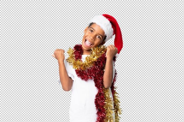Afroamerikanerjunge mit weihnachtshut einen sieg feiernd