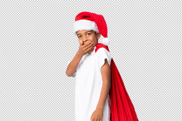 Afroamerikanerjunge mit weihnachtshut und nehmen einer tasche mit geschenken und handeln der überraschungsgeste