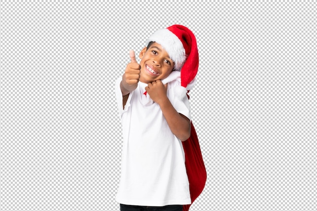 Afroamerikanerjunge mit weihnachtshut und nehmen einer tasche mit geschenken und mit dem daumen oben